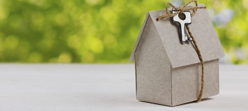 Cardboard home model wrapped in keys to new home.