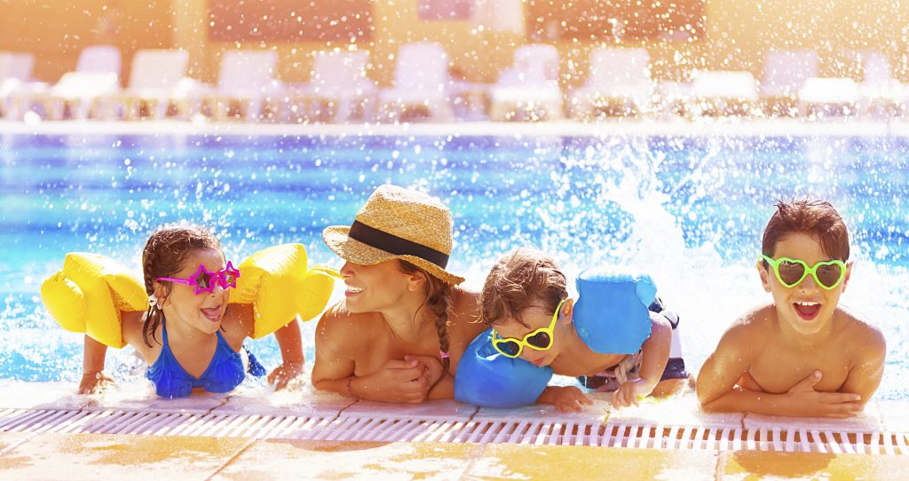 Family enjoying summer fun at home and in the pool
