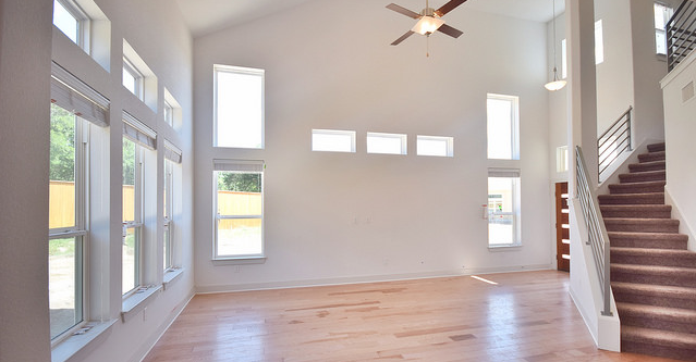 A spacious floor plan with an entry into a living room with staircase.
