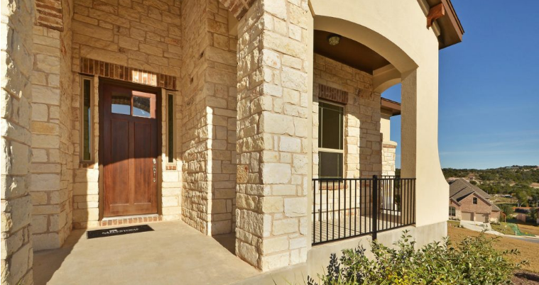 View of stone exterior and hill country from front porch of West Cypress Hills home.