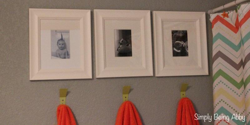 Towels on hooks below kids' pictures in bathroom.