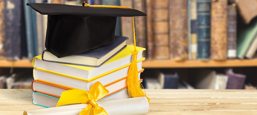 Graduation hat on top of books near diploma