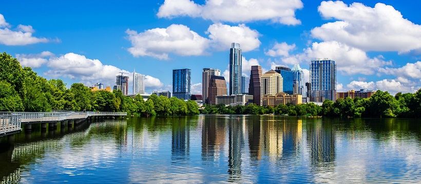 Blue skies and water surrounding Austin, Texas skyline.
