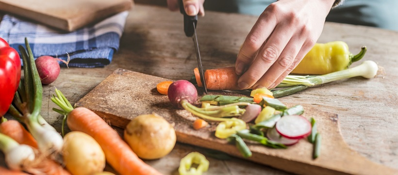 Persona cutting vegetables on cutting board.