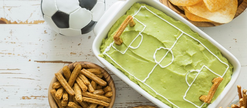 Guacamole and pretzels set out for a game-day party.