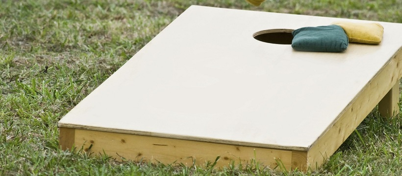 Bean bag toss game set outside for a game-day party.