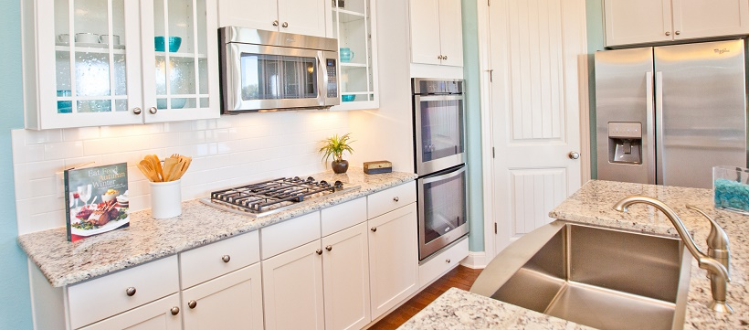 A white kitchen with blue walls, granite, and stainless steel appliances