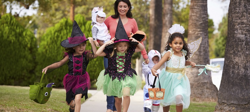 Children trick-or-treating on Halloween with an adult woman