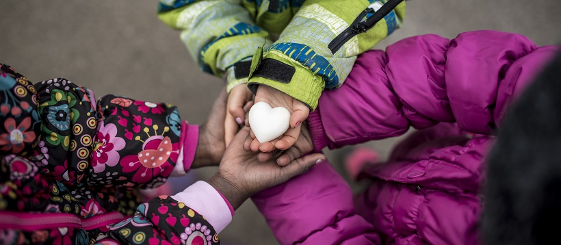 Children wearing coats and holding hands with heart in the middle