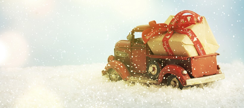 Toy truck carrying Christmas gift through fake snow