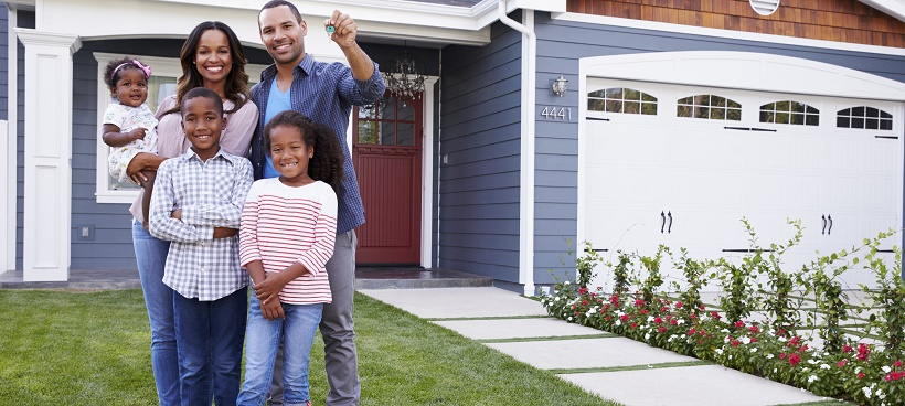 Family outside of new home as the dad holds keys in his hand