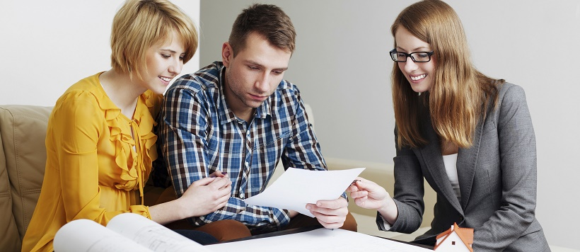 Couple meeting with real estate agent to discuss when to buy a home