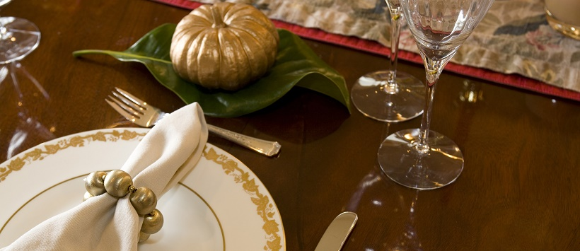 Simple Thanksgiving table decor with plates, silverware, and a pumpkin