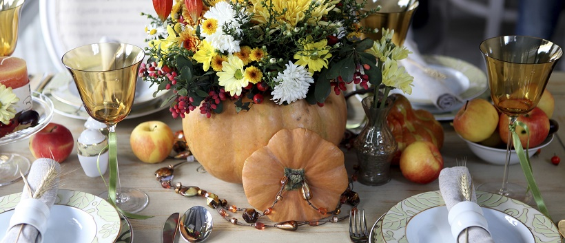Pumpkin filled with flowers as a centerpiece for Thanksgiving table decor