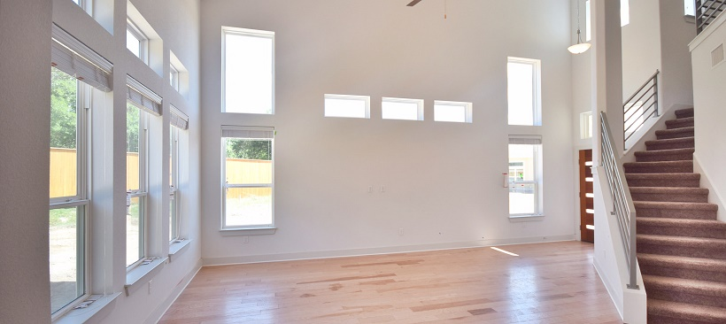 Living room of a move-in ready home with windows and hardwood flooring