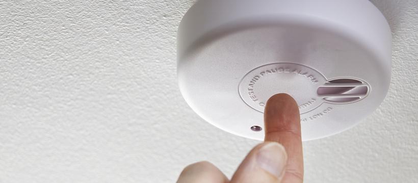 Person checking smoke detector