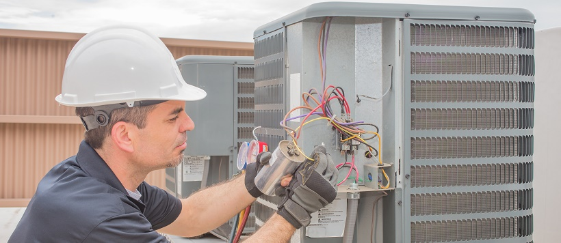Man working on HVAC for a home winterization plan