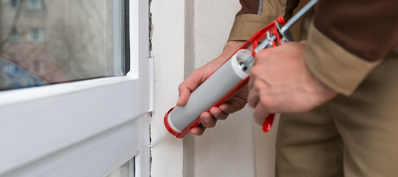 Person caulking window to help with home winterization plan