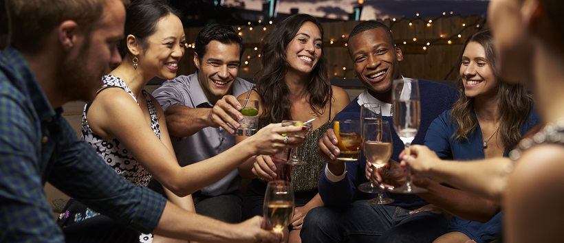 Group of younger adults enjoying downtown nightlife with drinks at a bar.