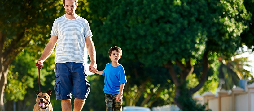 Dad walking with his son and a dog down a suburban street.