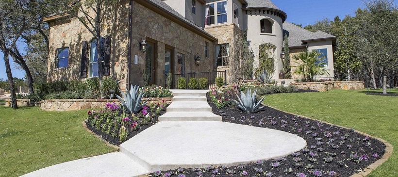 Two-story new Austin home with gorgeous landscape and stairway winding up to the front door