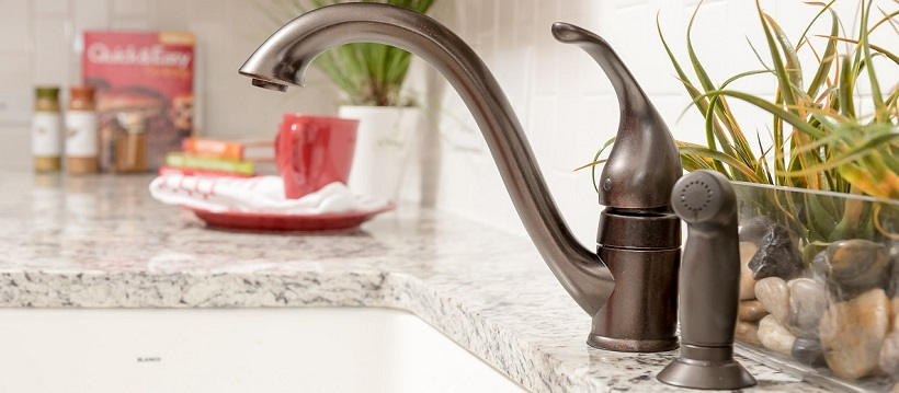 Brushed bronze faucet and white granite countertop of a kitchen in a new Austin home