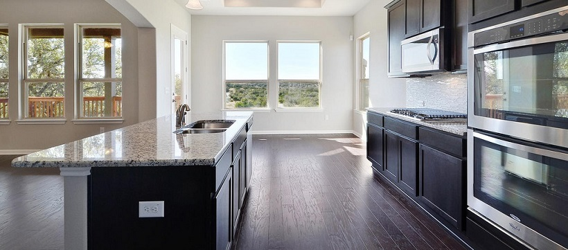 Kitchen with granite countertops, dark brown cabinetry and a Hill Country view