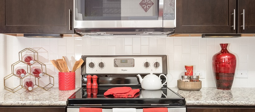 A new Austin home kitchen with brown cabinetry and red décor