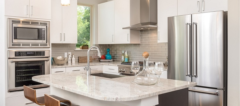 Modern kitchen with white cabinetry, white granite and stainless steel appliances