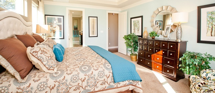 Blue walls surrounding bed with blue and brown bedspread in a new Austin home