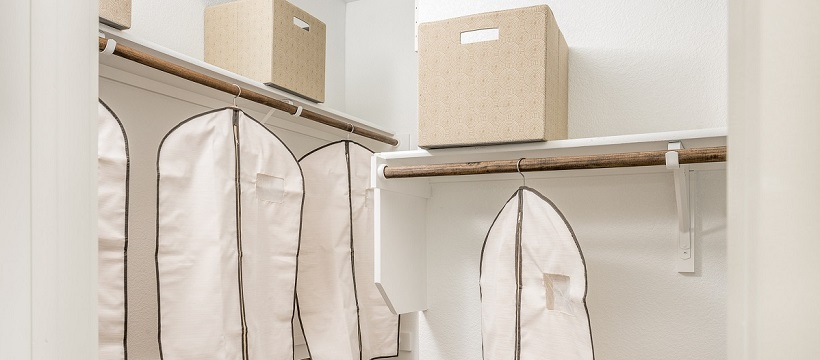 A new Austin home's walk-in closet with storage boxes and clothing bags