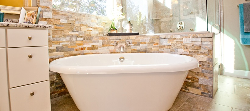 White porcelain tub surrounded by textured stone wall and glass shower in a new Austin home