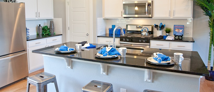 Contemporary white kitchen with blue home décor items like napkins and cooking utensils.