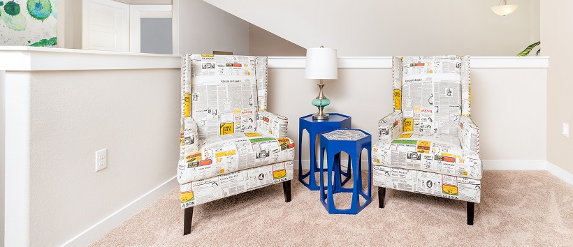 Two bright blue modern end tables between newspaper-patterned armchairs with orange accents.