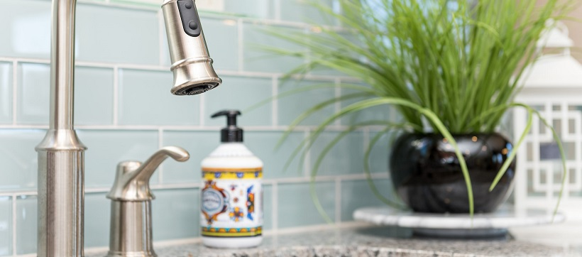Baby blue tiled backsplash behind stainless steel faucet in kitchen.