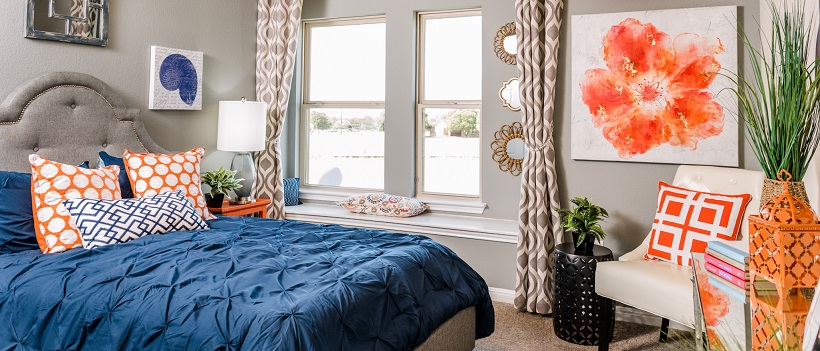 Bedroom with blue bedspread and orange and white polka dot pillows.