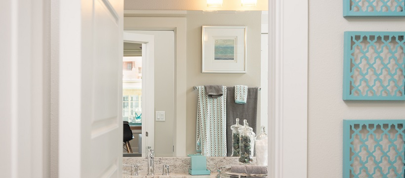Looking into white bathroom with light blue accents from hallway.