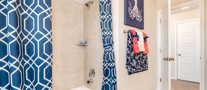 Navy blue shower curtains and navy towels and picture frame in white bathroom.