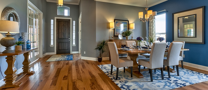 Entryway and dining room with hardwood floor and blue accent wall and decor.