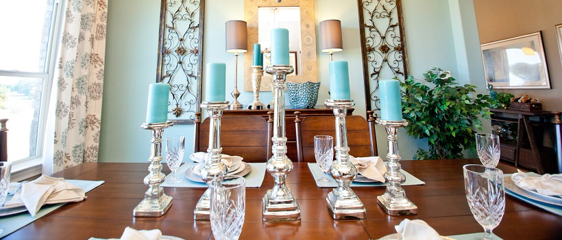 Light blue walls in dining room with wooden furniture and blue candles on candlesticks.