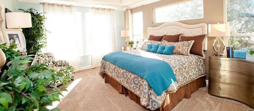 Light streaming in large bedroom with brown and blue bedding on bed.