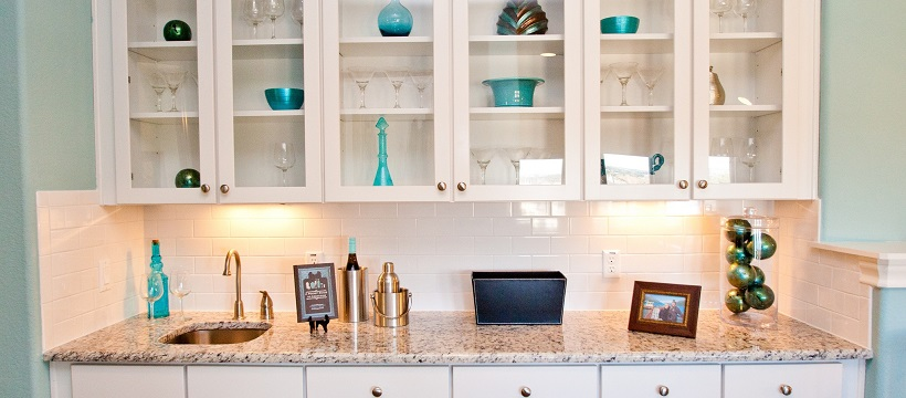 Light blue walls surround white cabinetry with glass covers showing blue home decor ideas inside each cabinet.