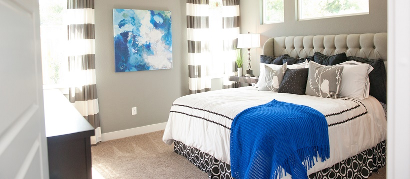 Bedroom with gray walls, a blue and white painting, and a blue throw on a white and black bedspread.
