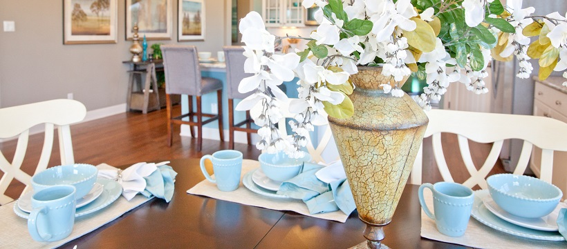 Light blue dining set around floral centerpiece on brown table in breakfast room.