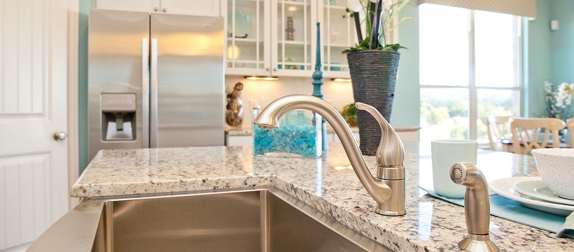 Close up of a stainless steel sink and faucet surrounded by a granite countertop in a blue and white kitchen.