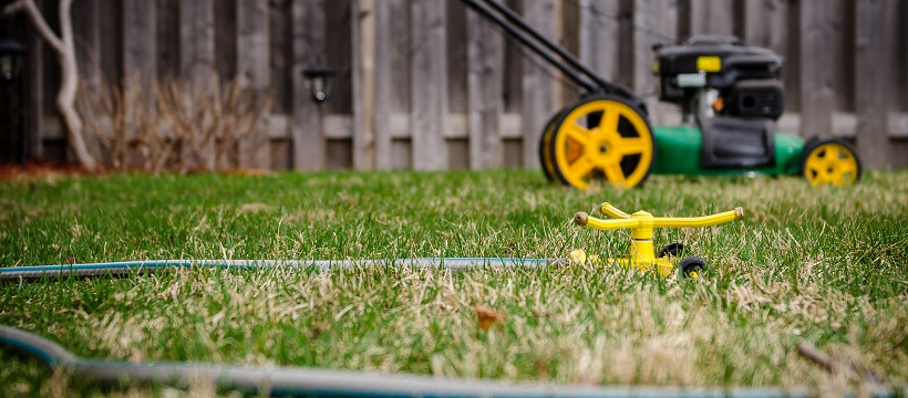 Lawnmower and sprinkler with attached hose sitting on lawn in front of fence.