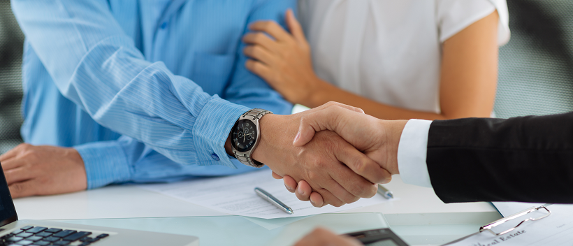 Couple starting the moving timeline while man shakes business man's hand