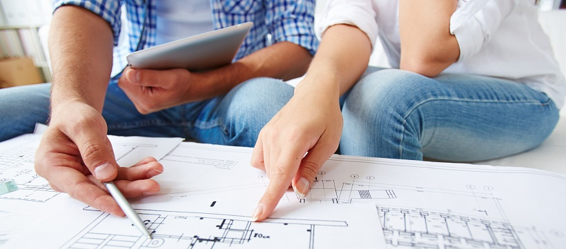 Close up of couple reviewing the floor plans to their new home as a part of their moving timeline plan.