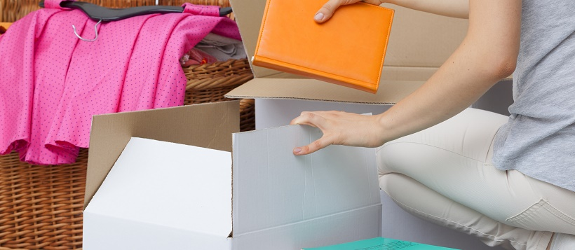 Woman working on moving timeline by packing up books and clothing.