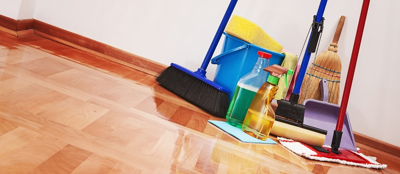 A variety of cleaning supplies leaning against wall and sitting on hardwood floor.